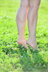 Woman standing on tiptoe on green grass. Close up body parts