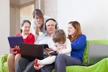 Happy family enjoys   with few various laptops