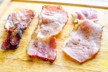 Three strips of cooked Canadian bacon
