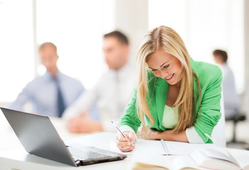attractive businesswoman taking notes in office