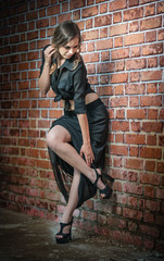 Charming young brunette woman in black dress near brick wall