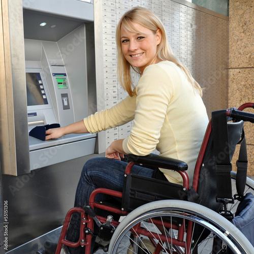Frau im Rollstuhl bedient Geldautomaten