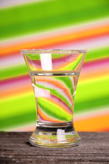 A glass of clear liquid on a bright background