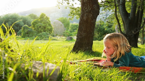 Little girl is reading a book in the park.