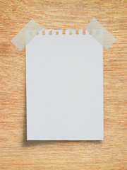 White torn paper note with scothch tape on wood board