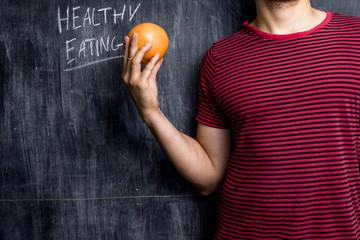 Man promoting healthy eating in front of blackboard