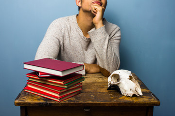 Student with skull and books is contemplating