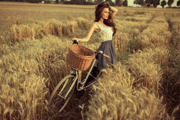 Woman with bike resting on wheat field at sunset