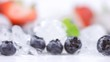 Strawberries and blackberries with ice cubes, on white