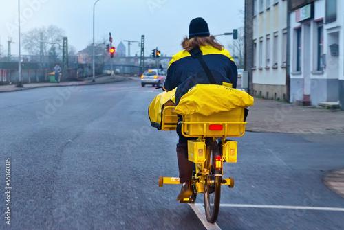 Leinwandbild Motiv Postbotin auf Fahrrad am Morgen im Winter