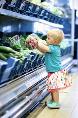 Adorable baby girl takes radish from shelf in groccery shop