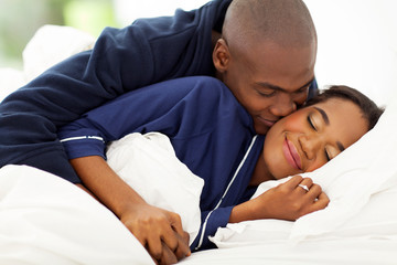 african man kissing wife in bed