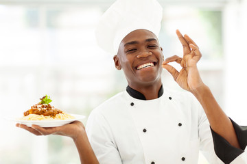 professional African chef holding delicious spaghetti