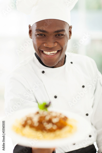 African chef in hotel kitchen presenting pasta