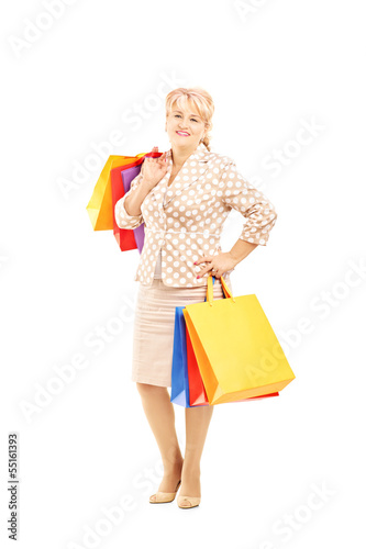 Full length portrait of a blond mature woman holding shopping ba