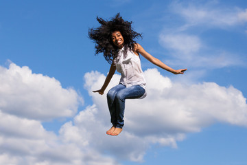 Outdoor portrait of a teenage black girl jumping over a blue sky