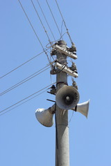 Telegraph poles with speakers and cables against a blue sky