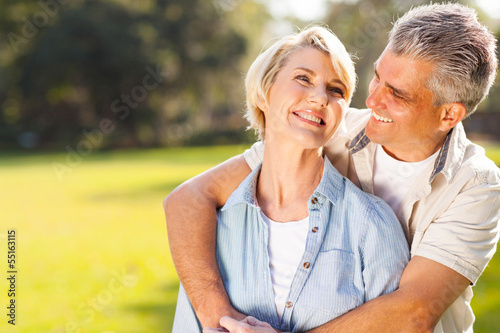 middle aged couple embracing outdoors - 55163115