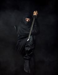 Ninja with sword on black in smoke