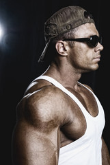 Portrait of a handsome muscular man wearing a cap standing in pr