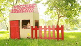 Video of happy little children sitting in playhouse