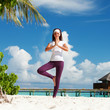 Pretty woman doing yoga exercises on the tropical beach