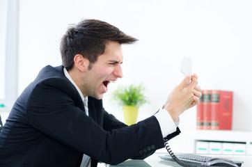 businessmann schreit ins telefon