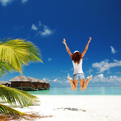 happy young woman jumping on the tropical beach