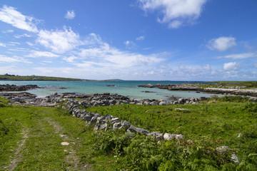 A turquoise beach and green field, Connemara