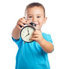 cheerful child holding a black alarm clock
