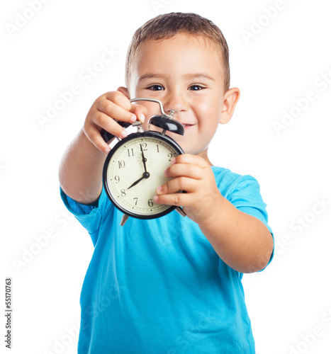 cheerful child holding a black alarm clock