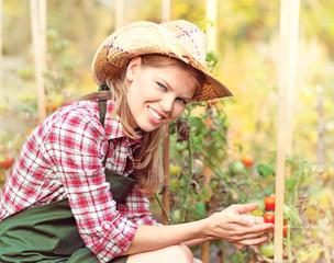 Young Caucasian gardener holding ripe vegetables in kaleyard