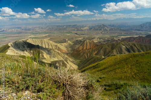 Saimaly-Tash valley with mountains on horizon and blue sky with