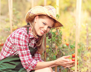 Smiling female grower touching red tomato in the garden