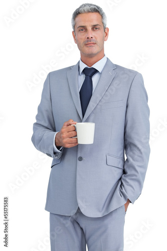 Serious businessman standing with coffee