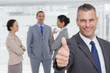 Cheerful manager showing thumb up with employees in background