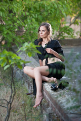 Charming brunette woman in black dress sitting on a brick  wall