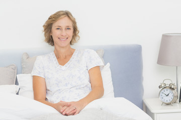 Blonde woman sitting in bed smiling at camera