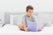 Concentrated little boy sitting on bed reading book