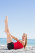 Athletic blonde doing pilates core exercise smiling at camera