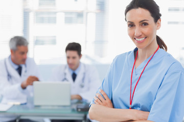 Doctors using laptop and a smiling nurse crossed her arms