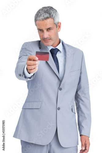 Handsome businessman holding and looking at credit card