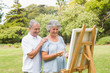 Cheerful retired woman painting on canvas with husband