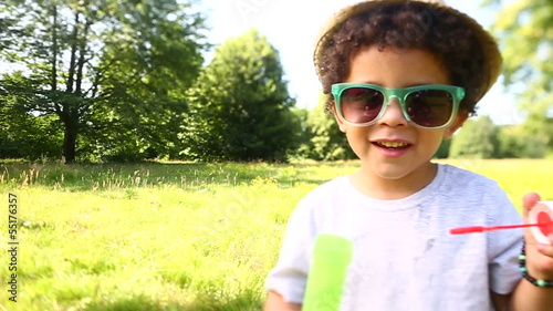 Happy boy blowing bubbles in garden or nature