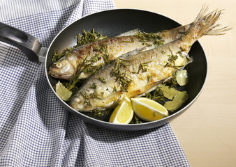 Roastes fish in a pan with lemon
