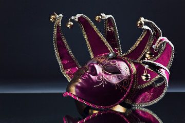 Venetian mask with bells on a mirror table