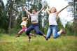 Children jump on lawn in summer forest