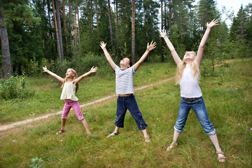 Children on lawn of forest and enjoy life in sports