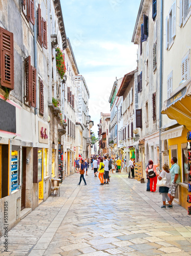 People walk the old town streets in Porec, Croatia.