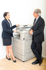 Colleagues talking at copying machine in the office